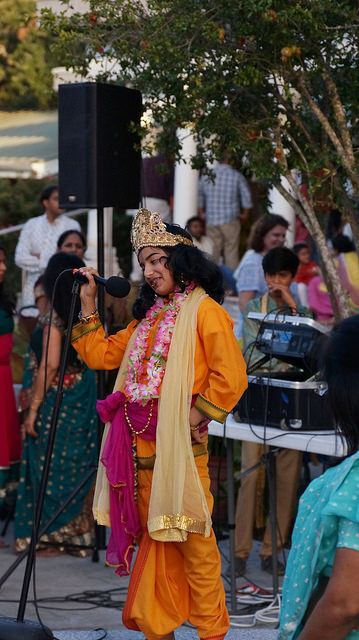 Krishna storytelling and asking questions on outdoor stage