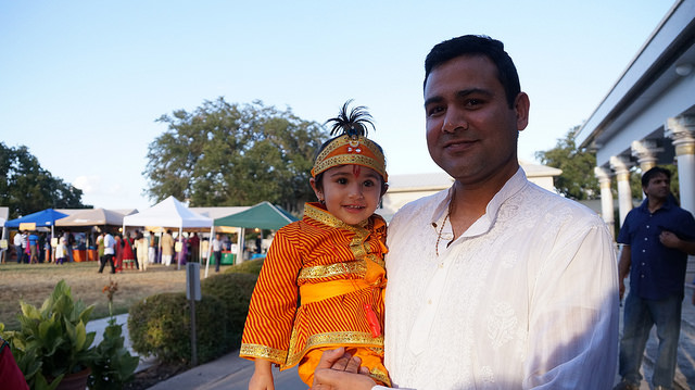beautiful baby krishna posing on stage with Daddy