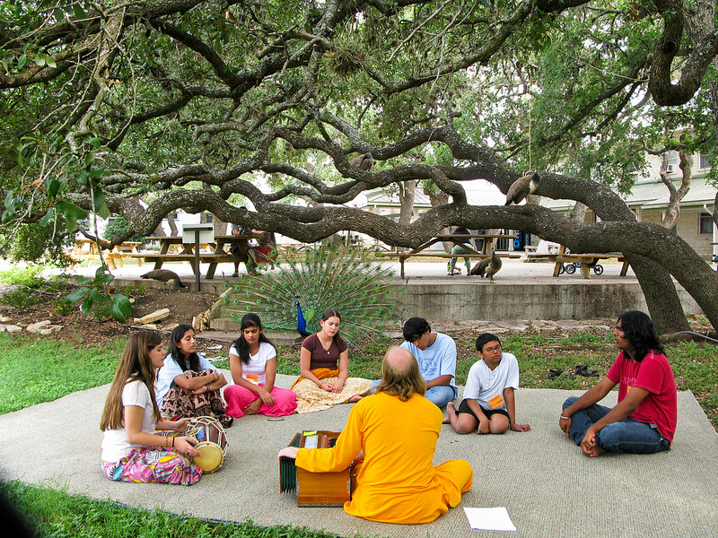 Like the forest ashrams of ancient India, a quiet satsang is enjoyed under the trees in Radha Madhav Dham.