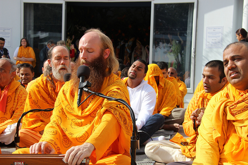 While Swami Nikhilanand leads the devotees in kirtan...